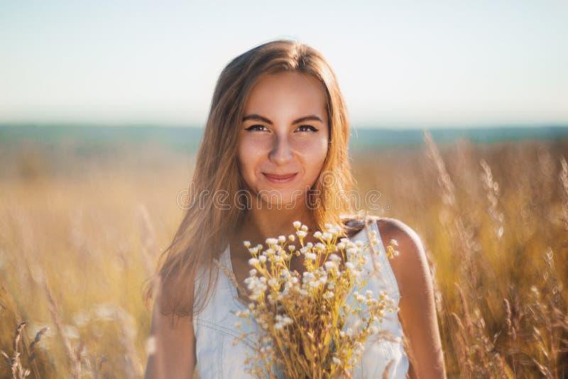 Atrakcyjna młoda kobieta stoi ono uśmiecha się w łące na zmierzchu obraz stock