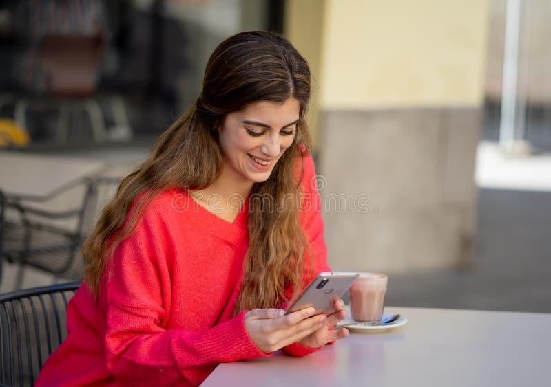 Atrakcyjna młoda kobieta używa mądrze telefonu komórkowego datowanie app w sklepu z kawą outside tarasie zdjęcie royalty free