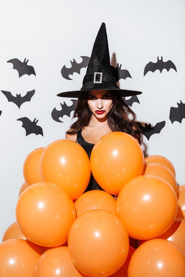 Atrakcyjna młoda kobieta w czarownicy Halloween kostiumu z pomarańczowymi balonami fotografia royalty free