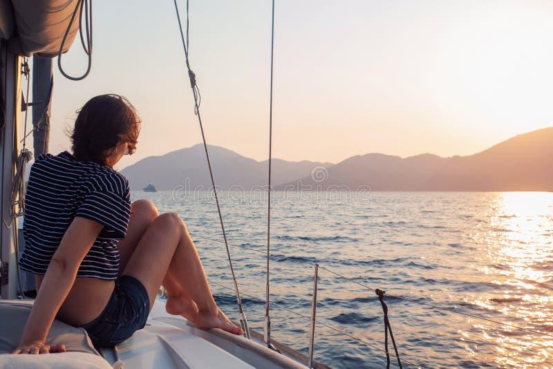 Atrakcyjna młoda kobieta w paskowej koszulce cieszy się zachodem słońca na pokładzie jachtu żeglarskiego Dziewczyna jachtarz fotografia stock