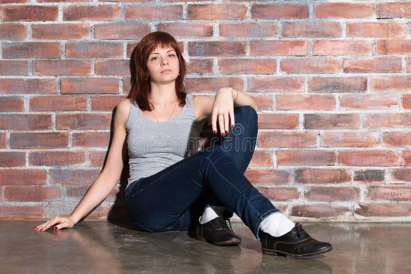Atrakcyjna młoda kobieta w przypadkowych ubraniach, niebieskich dżinsach i kamizelce popielatych, jest przyglądająca kamera i uśm zdjęcie stock