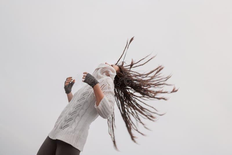 Atrakcyjna młoda kobieta w pulowerze ma zabawę outdoors fotografia stock