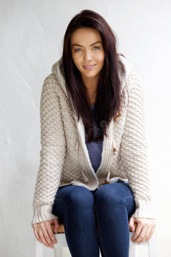 Atrakcyjna młoda kobieta w wełna puloweru obsiadaniu na krześle fotografia stock