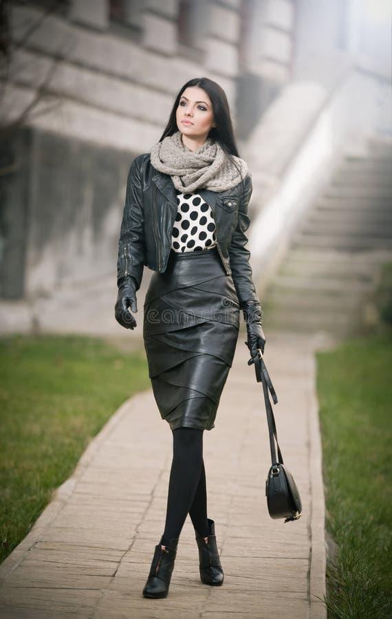 Atrakcyjna młoda kobieta w zimy mody strzale. Piękna modna młoda dziewczyna w czarnej skórze budzi się na alei. Elegancka kobieta zdjęcia royalty free