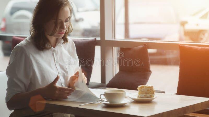 Atrakcyjna młoda kobieta wydaje czasu wolnego obsiadanie w kawiarniach, cieszący się świeżego czytanie i kawę kobiety ` s magazyn zdjęcie royalty free
