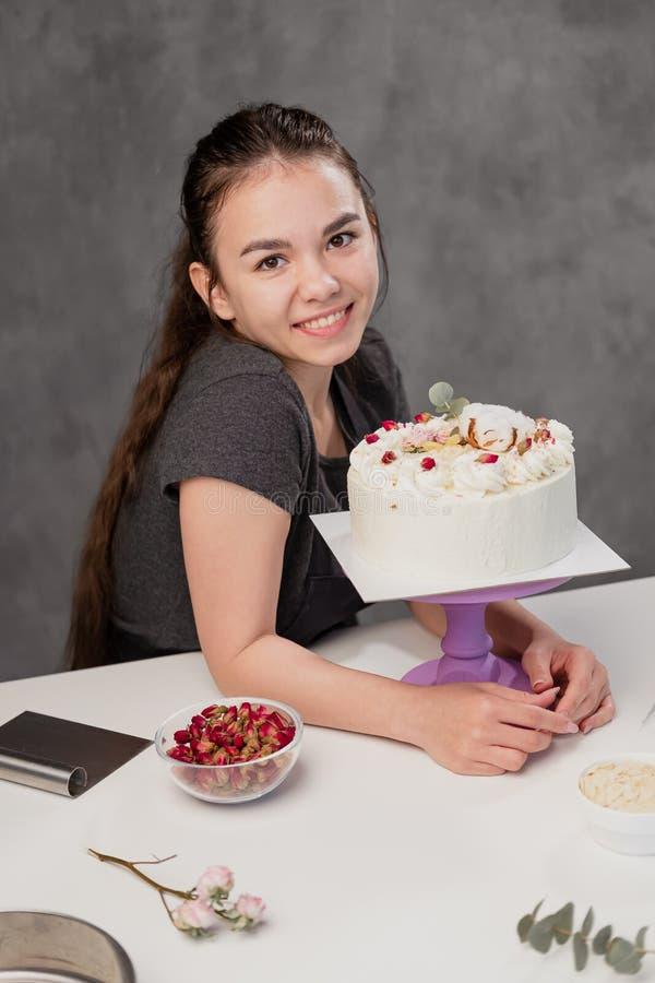 Atrakcyjna młoda kobieta wzrastał brunetki cukierniczka przedstawia białego tort z małymi czerwonymi kwiatami jedzenie obraz stock