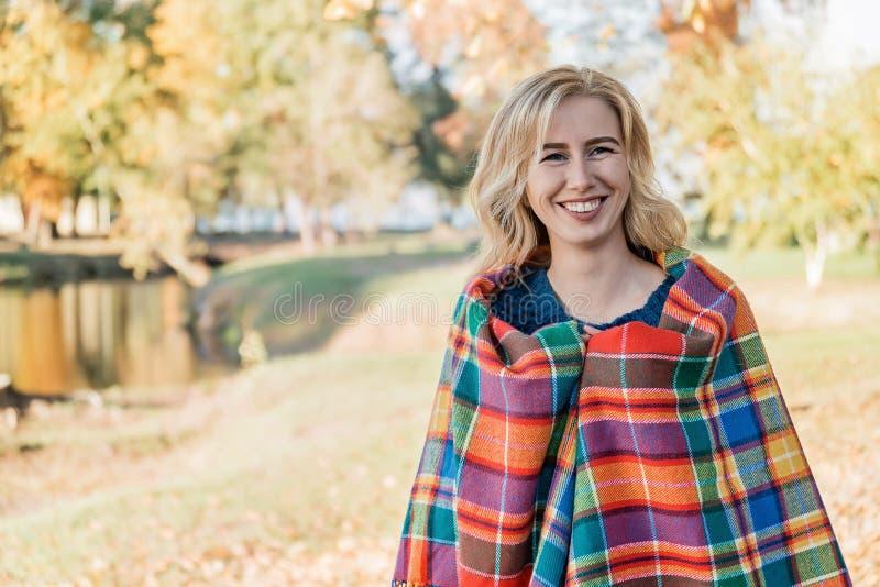 Atrakcyjna młoda kobieta z kędzierzawym włosy zawijającym w ciepłej koc i odprowadzeniu w jesień parku outside zdjęcia royalty free