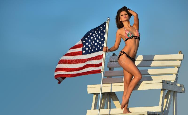 Atrakcyjna młoda kobieta z perfect schudnięcie napadu ciałem w bikini pozuje na ratownika wierza zdjęcia royalty free