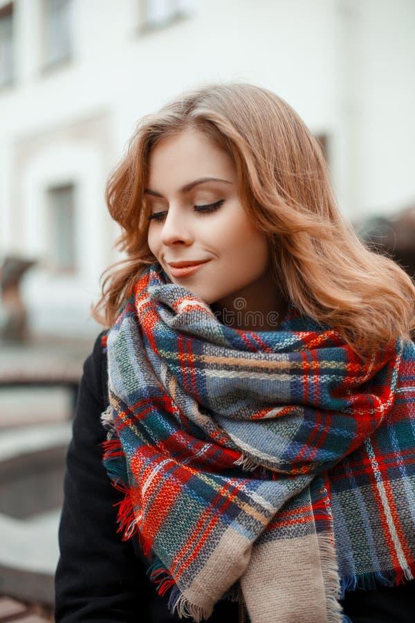 Atrakcyjna młoda kobieta z pięknym uśmiechem z kędzierzawym włosy w modnym grże żakiet z rocznika woolen szalikiem outdoors obrazy stock