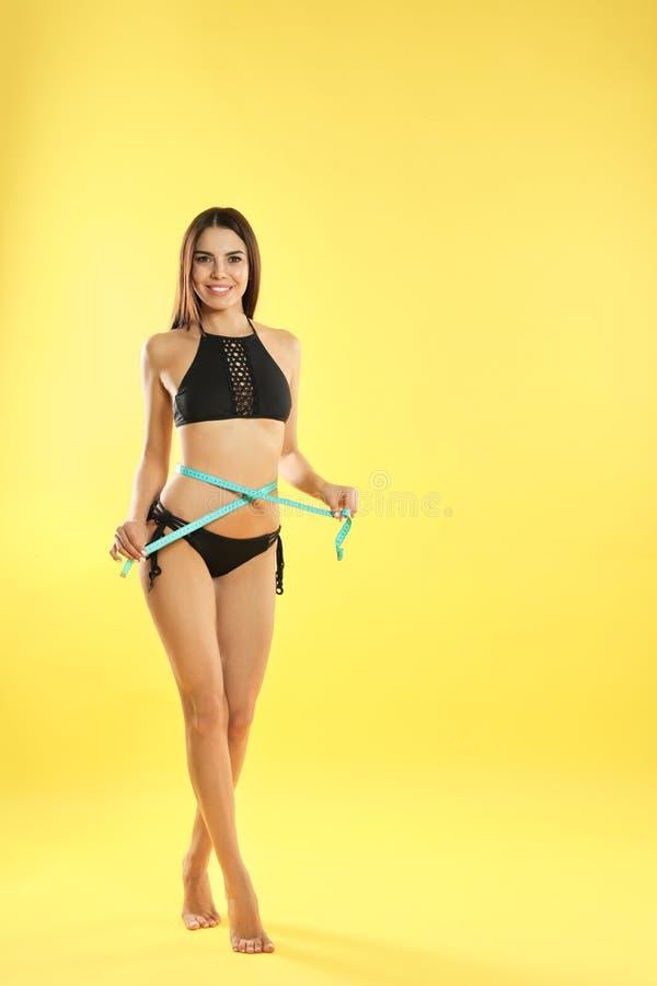 Atrakcyjna młoda kobieta z szczupłym ciałem mierzy jej talię zdjęcia royalty free