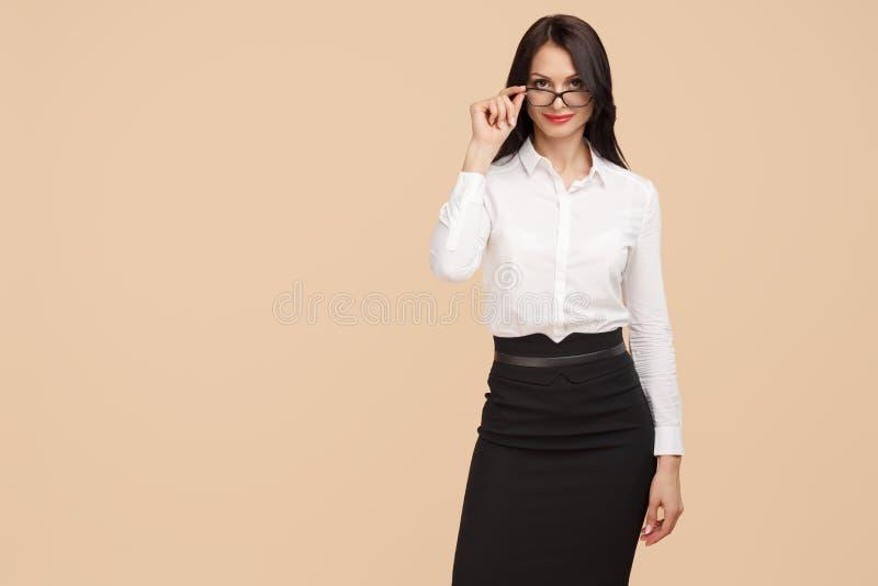 Atrakcyjna młoda nowożytna biznesowa kobieta stoi nad beżowym tłem Sukces i zwycięzcy pojęcie obrazy stock