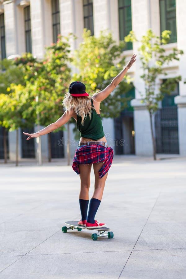 Atrakcyjna młoda przypadkowa kobieta jedzie deskorolka zdjęcie stock