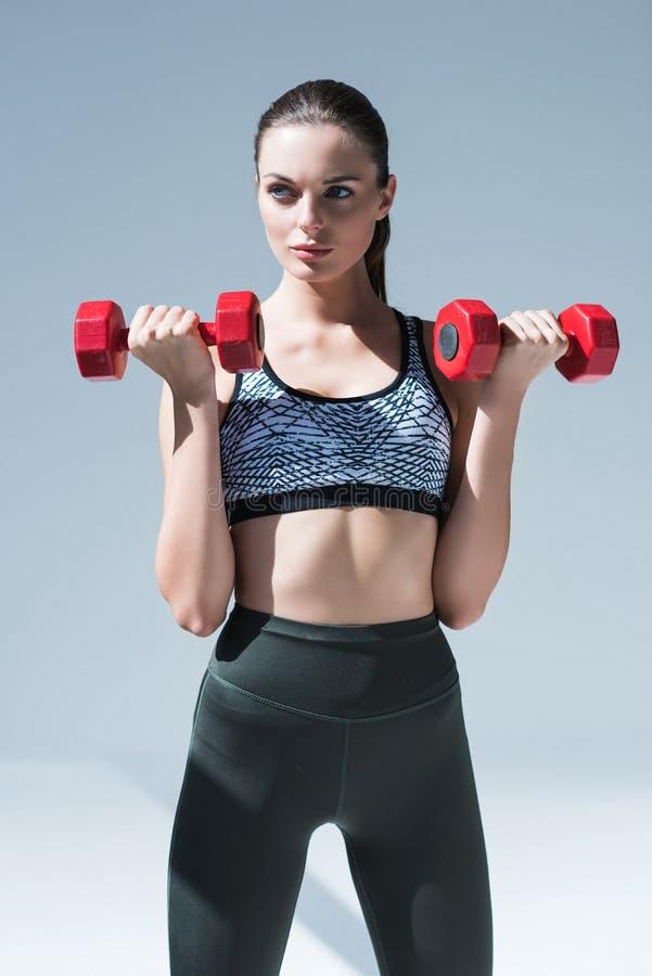 atrakcyjna młoda sportsmenka ćwiczy z dumbbells zdjęcie stock