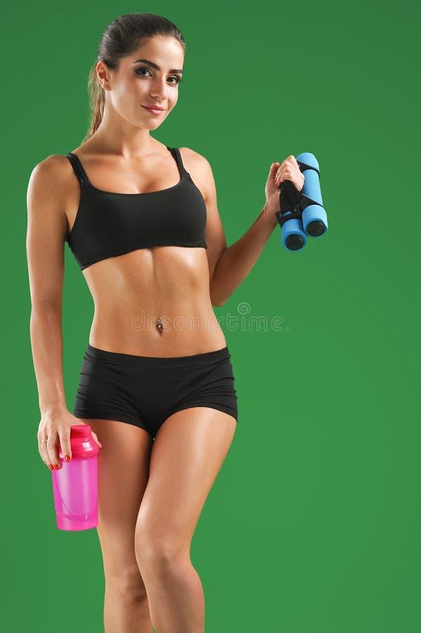 Atrakcyjna młoda sprawności fizycznej kobieta z sport butelką na zieleni bac obrazy stock