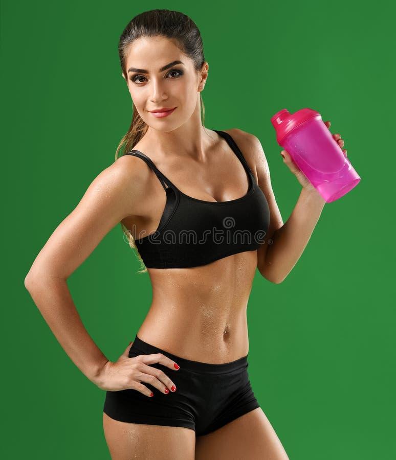 Atrakcyjna młoda sprawności fizycznej kobieta z sport butelką na zieleni bac fotografia stock