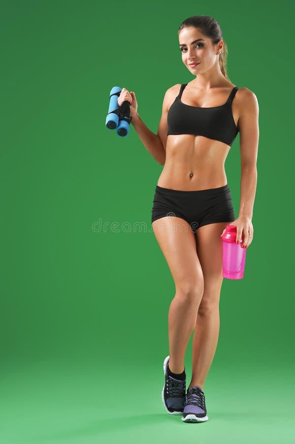 Atrakcyjna młoda sprawności fizycznej kobieta z sport butelką na zieleni bac fotografia royalty free