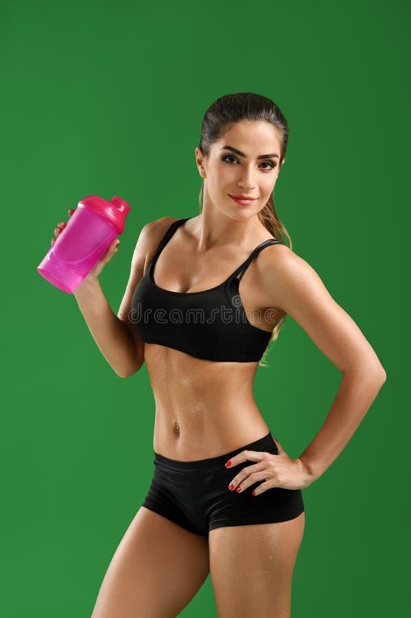 Atrakcyjna młoda sprawności fizycznej kobieta z sport butelką na zieleni bac zdjęcie stock