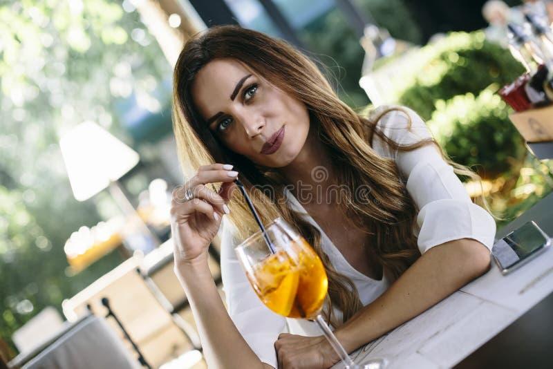 Atrakcyjna m?oda kobieta pije koktajl w cukierniany plenerowym zdjęcie stock
