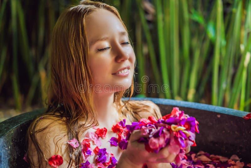 Atrakcyjna m?oda kobieta w sk?paniu z p?atkami tropikalni kwiaty i aromat?w oleje Zdroj?w traktowania dla sk?ry odm?adzania zdjęcia stock