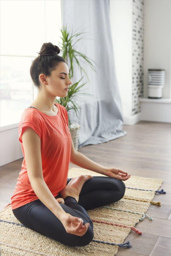 Atrakcyjna m?oda kobieta ?wiczy i siedzi w joga lotosowej pozyci podczas gdy odpoczywaj?cy w domu zdjęcia stock