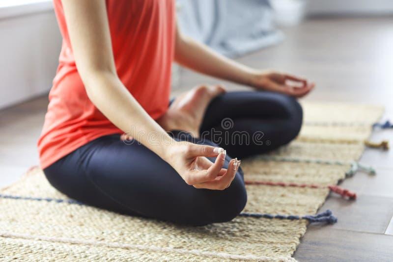 Atrakcyjna m?oda kobieta ?wiczy i siedzi w joga lotosowej pozyci podczas gdy odpoczywaj?cy w domu fotografia royalty free