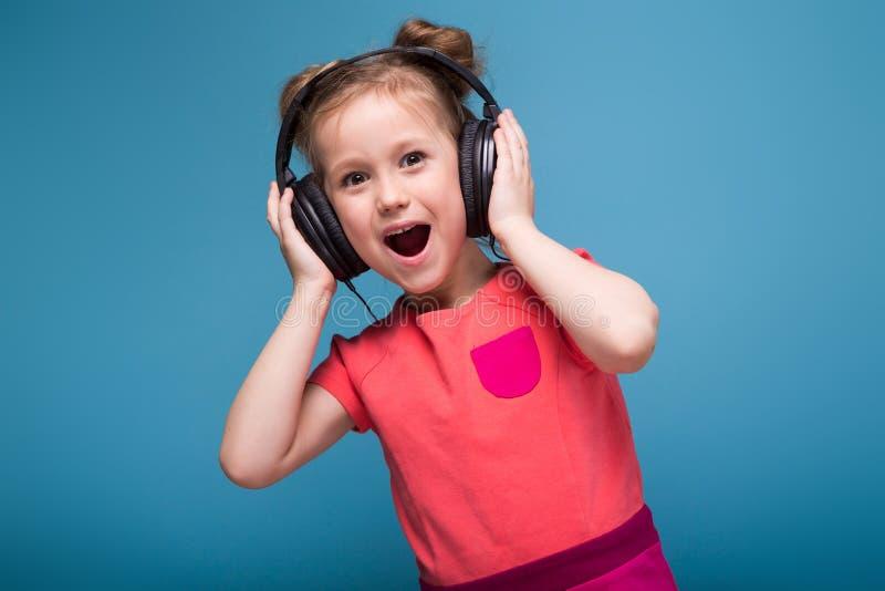 Atrakcyjna mała śliczna dziewczyna w menchia hełmofonach i sukni fotografia royalty free