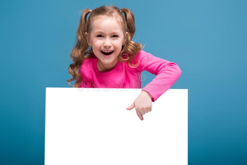 Atrakcyjna mała śliczna dziewczyna w różowej koszula z małpiego i błękitnego spodnie chwyta pustym plakatem obrazy stock