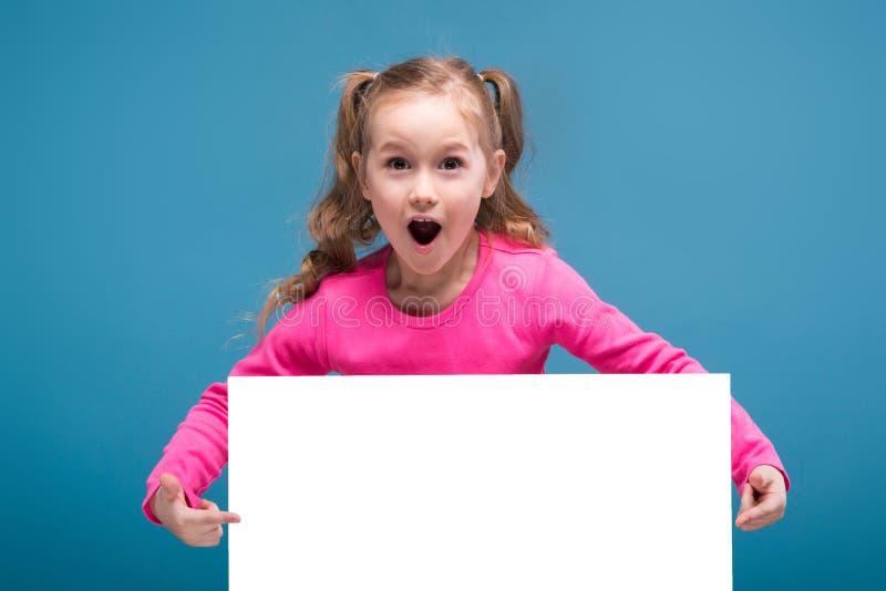Atrakcyjna mała śliczna dziewczyna w różowej koszula z małpiego i błękitnego spodnie chwyta pustym plakatem zdjęcia royalty free