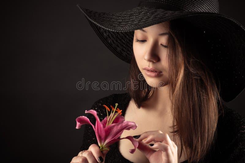 Atrakcyjna Mieszana Biegowa Koreańska Rosyjska dziewczyna z leluja kwiatem obrazy royalty free