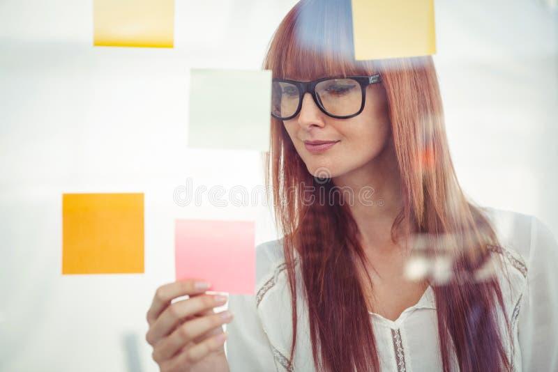 Atrakcyjna modniś kobieta patrzeje kleiste notatki zdjęcia royalty free