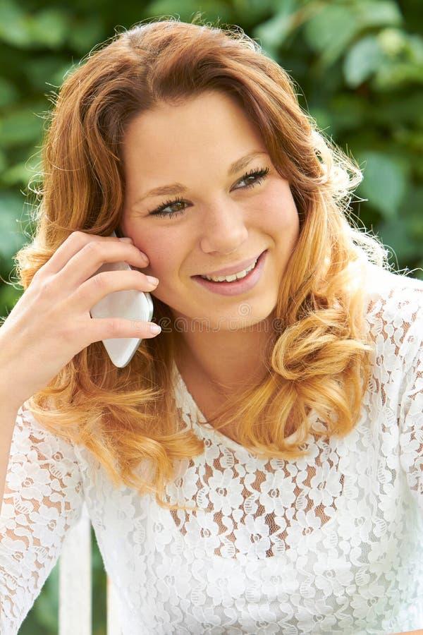 Atrakcyjna nastoletnia dziewczyna Opowiada Na telefonie komórkowym zdjęcie stock