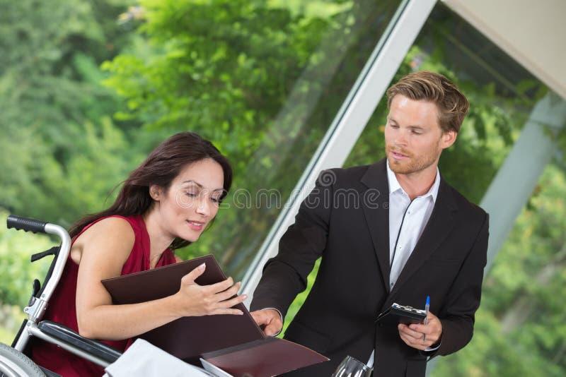 Atrakcyjna niepełnosprawna kobieta rozkazuje kelner przy restauracją obrazy stock