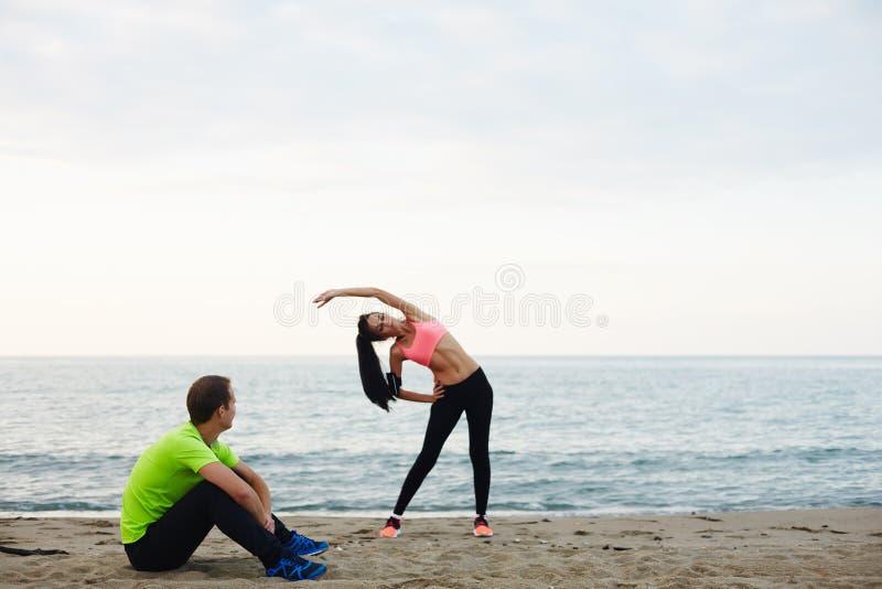 Atrakcyjna para małżeńska angażował w rozciąganiu na nabrzeżu fotografia stock