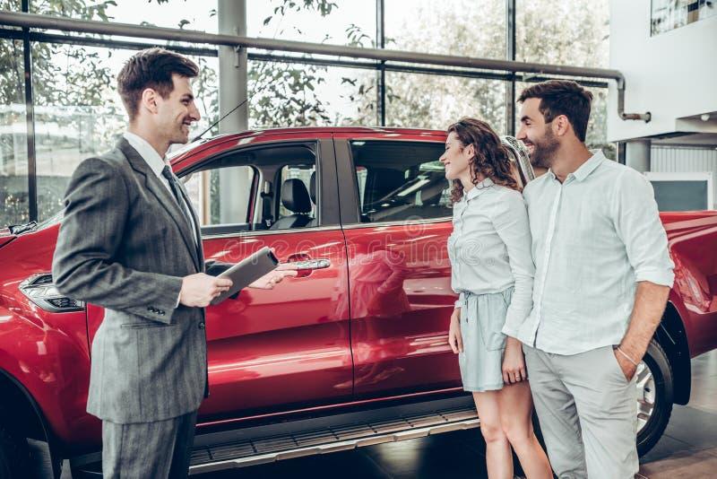 Atrakcyjna para opowiada samochodowy sprzedaż kierownik w luksusowym przedstawicielstwo firmy samochodowej i patrzeje pięknego cz fotografia stock