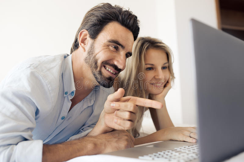 Atrakcyjna para używa laptop w sypialni obrazy stock