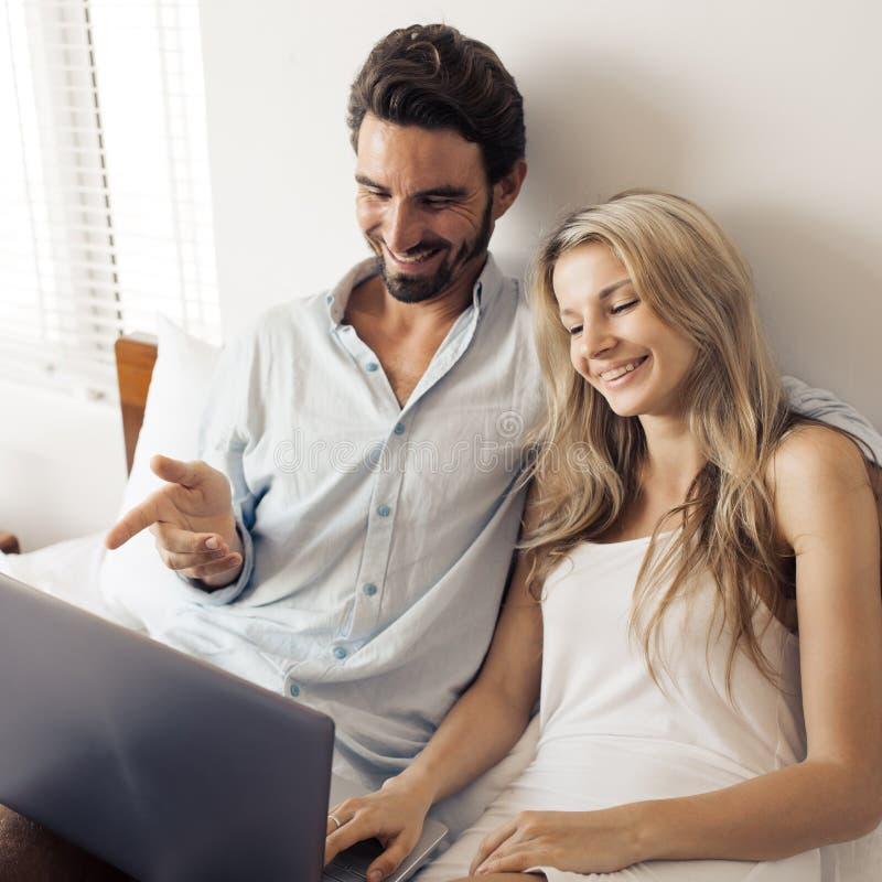 Atrakcyjna para używa laptop w sypialni obrazy royalty free