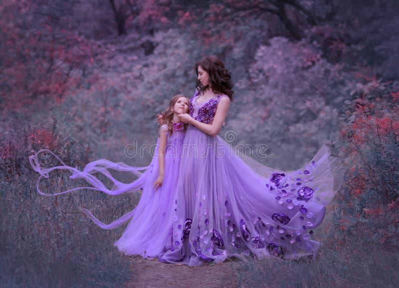 Atrakcyjna potomstwo matka z ciemnym falistym włosy i jej małą córką stoi wpólnie w lesie w zadziwiać długo, obraz royalty free