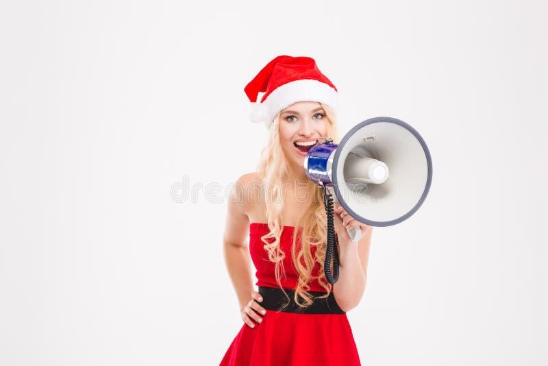 Atrakcyjna pozytywna kobieta opowiada na megafonie w Santa Claus kostiumu zdjęcie royalty free