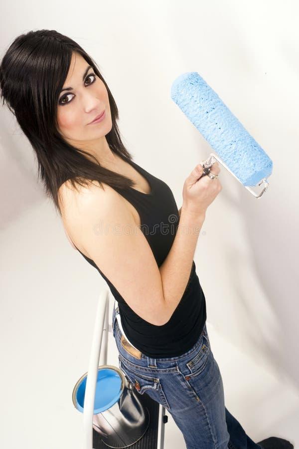 Atrakcyjna Przydatna kobieta Używa farba rolownika farby Błękitnego projekt zdjęcia royalty free