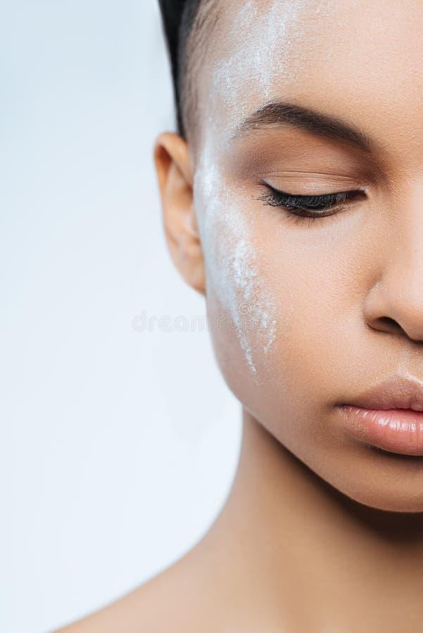 Atrakcyjna przyjemna kobieta ma bielu proszek na jej twarzy zdjęcia royalty free