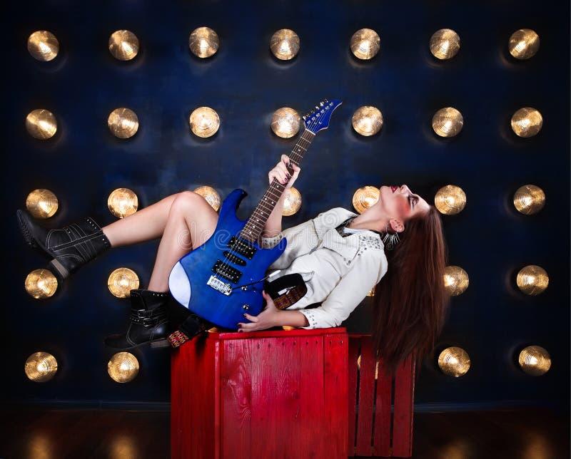 Atrakcyjna punkowa dziewczyna z chłodno uzupełniał mienie gitarę fotografia royalty free
