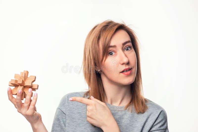 Atrakcyjna 24 roczniak biznesowej kobiety patrzeje wprawiać w zakłopotanie z drewnianą łamigłówką zdjęcia stock
