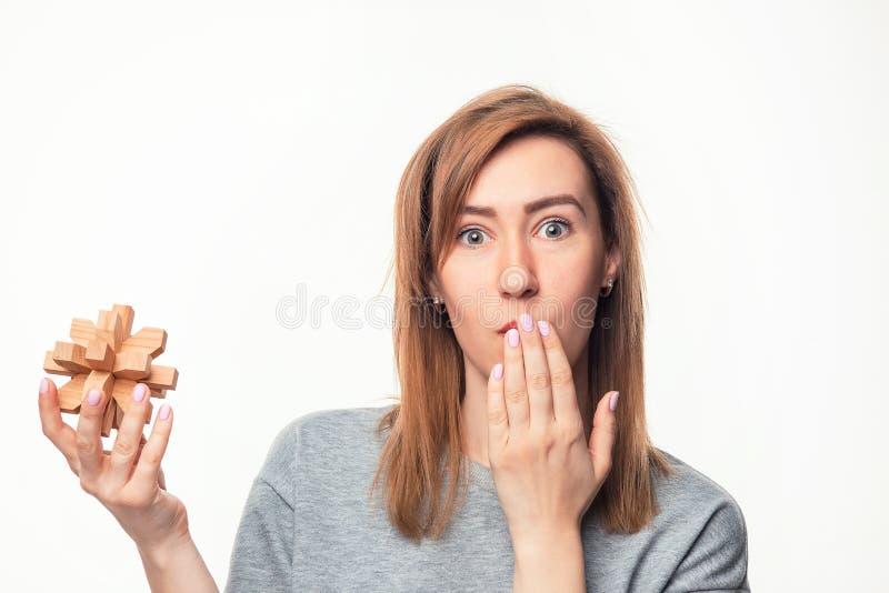 Atrakcyjna 24 roczniak biznesowej kobiety patrzeje wprawiać w zakłopotanie z drewnianą łamigłówką obrazy royalty free