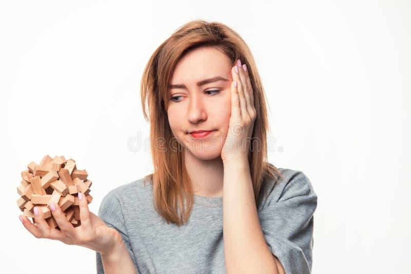 Atrakcyjna 24 roczniak biznesowej kobiety patrzeje wprawiać w zakłopotanie z drewnianą łamigłówką fotografia royalty free