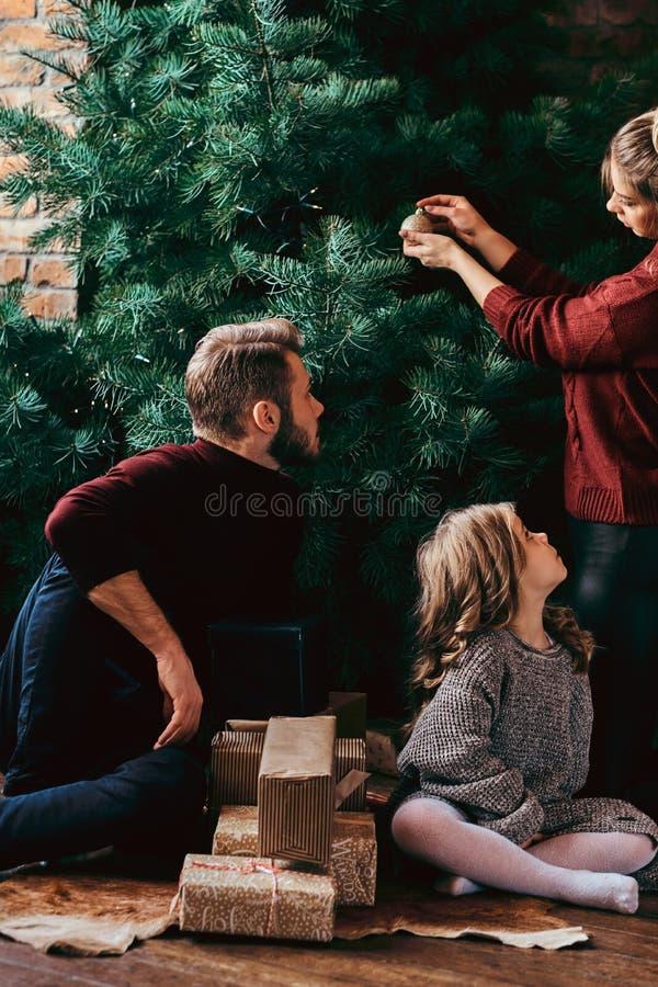 Atrakcyjna rodzina dekoruje choinki, otaczającej prezentami w domu obrazy stock