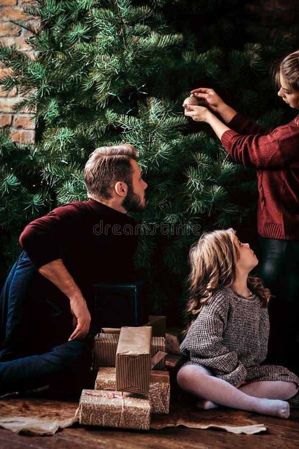 Atrakcyjna rodzina dekoruje choinki, otaczającej prezentami w domu zdjęcie royalty free