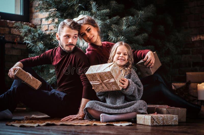 Atrakcyjna rodzina otwiera teraźniejszość podczas gdy siedzący na podłodze obok choinki obraz royalty free