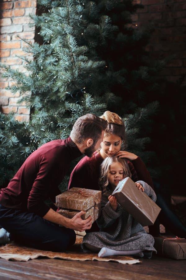 Atrakcyjna rodzina otwiera teraźniejszość podczas gdy siedzący na podłodze obok choinki obrazy royalty free