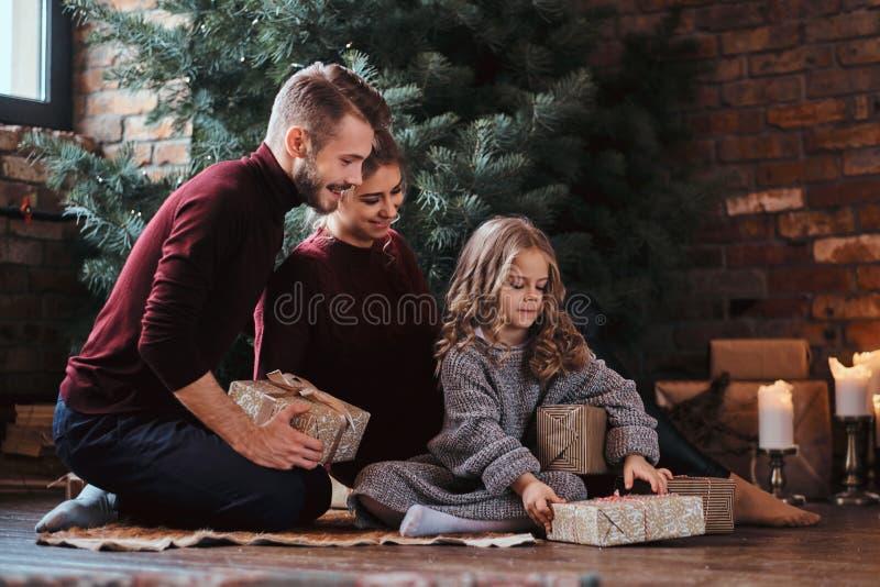 Atrakcyjna rodzina otwiera teraźniejszość podczas gdy siedzący na podłodze obok choinki zdjęcie stock