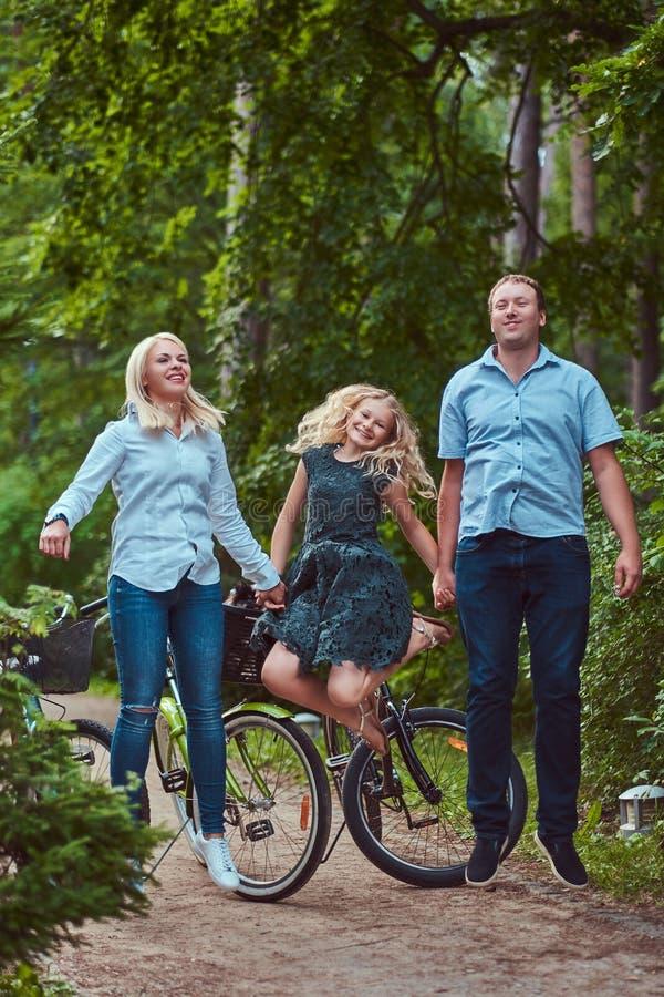 Atrakcyjna rodzina ubierał w przypadkowych ubraniach na rowerowej przejażdżce, w parku, zabawę i doskakiwanie obrazy stock
